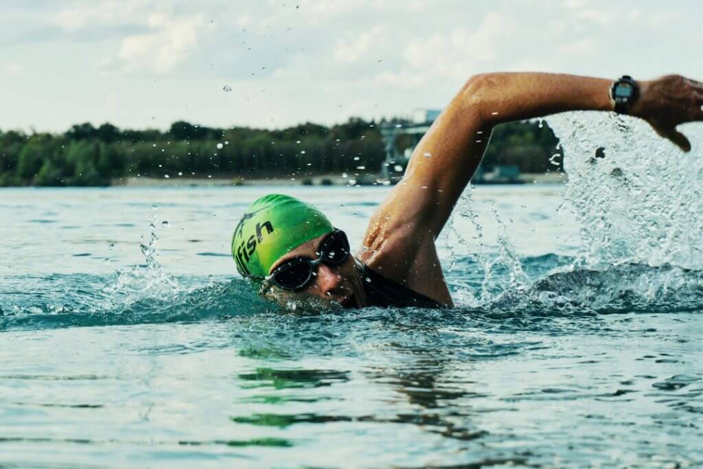 Man swimming in a lake with a green skull cap and with protective eyewear swimming goggles to keep his prosthetic eye safe.
