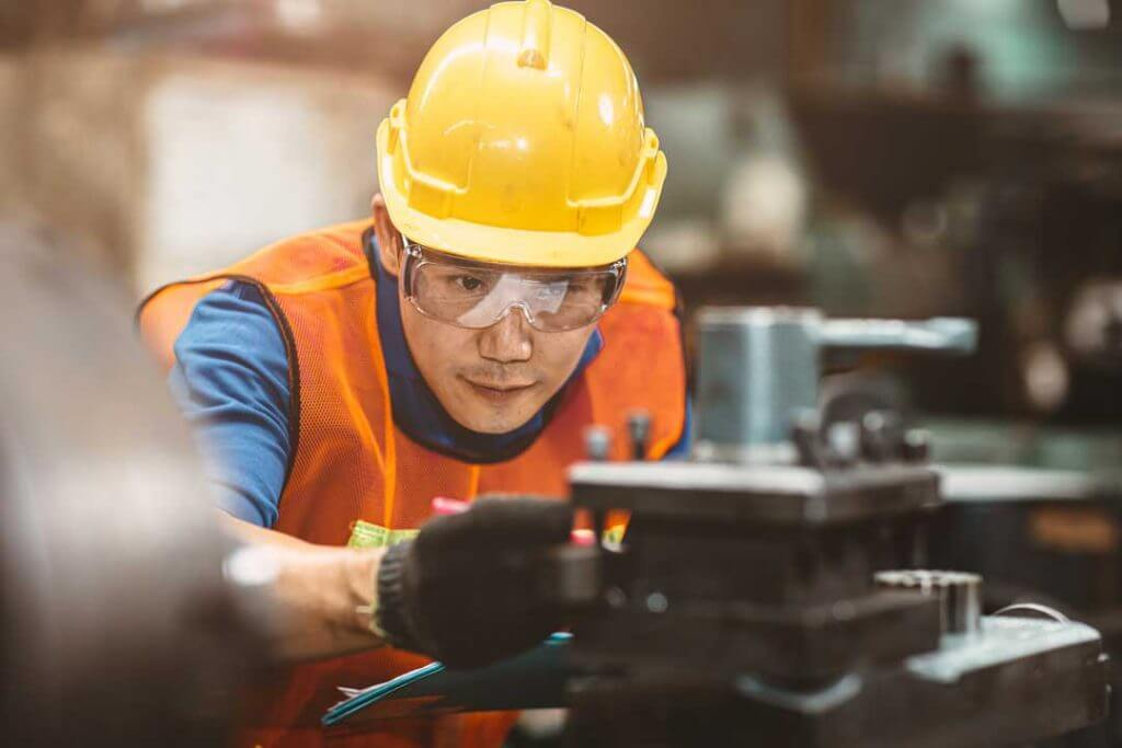 Factory worker in yellow hard hat protecting prosthetic eye from injury by wearing protective eyewear